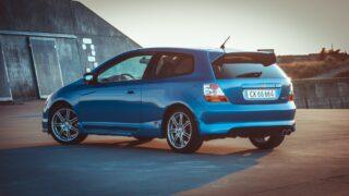 blue honda hatchback on concrete pavement